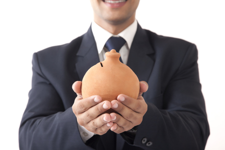 businesswear: Close-up of young professional man holding clay saving pot in both hands against white background