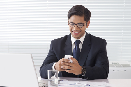 businesswear: Happy looking young professional man operating his mobile phone at office desk