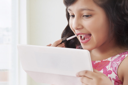 preadolescent: Cute girl putting on lipstick looking into mirror Stock Photo