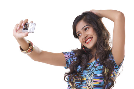 looking away from camera: Young woman taking self photo with camera