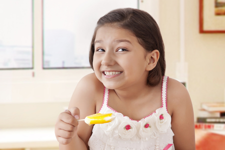 preadolescent: Girl eating ice cream popsickles