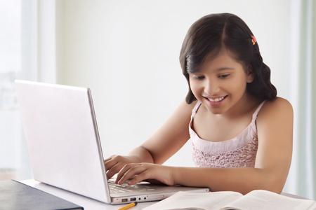 preadolescent: Portrait of smiling cute girl using laptop