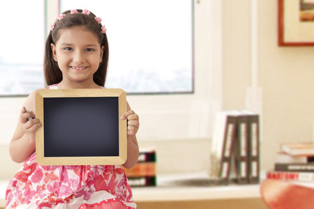 preadolescent: Girl smiling and holding slate