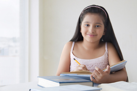 preadolescent: Portrait of cute girl doing homework