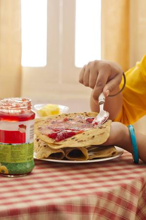 paratha: Woman spreading jam on paratha Stock Photo