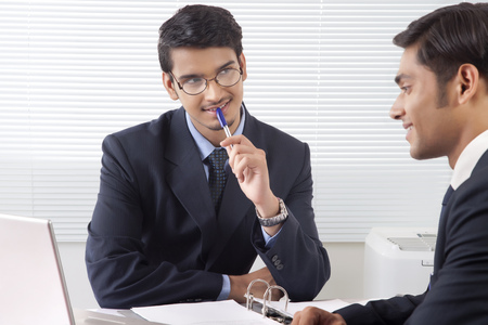 advice: Young professional man listening patiently to another professional man at office with smile on his face
