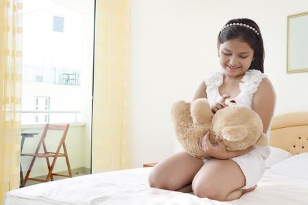 arrodillarse: Feliz sonriente niña jugando con el oso de peluche en la cama Foto de archivo