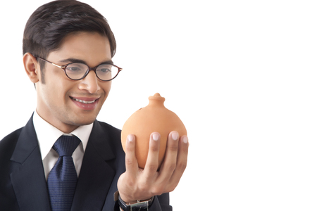 businesswear: Close-up of young professional man looking at clay saving pot in hand against white background Stock Photo