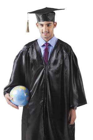 accomplishments: Young Male Graduate With Globe Stock Photo