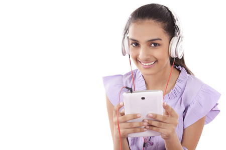 music background: Teenage Girls enjoying her music listening to a set of earphones attached to her tablet Stock Photo