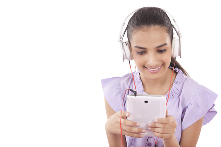 attached: Teenage Girls enjoying her music listening to a set of earphones attached to her tablet Stock Photo