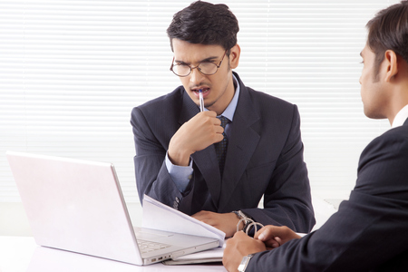 advice: Young professional man in deep thought holding pen between his teeth looking at laptop computer while discussing work with another professional man Stock Photo
