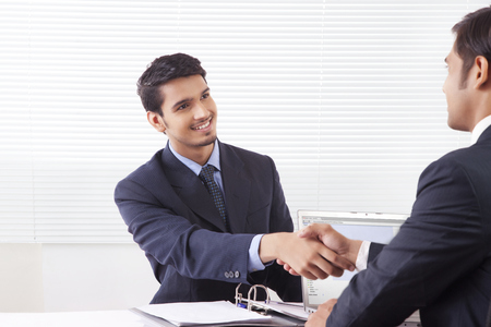advice: Two business men shaking hands with smile in office cabin