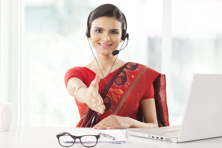 earpiece: Indian businesswoman wearing headset and smiling