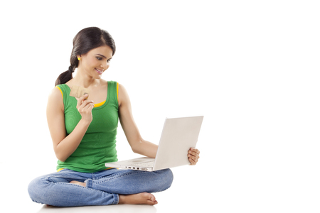 cross legged: Portrait of a young woman online shopping