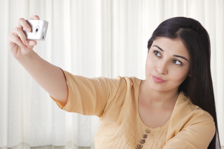 looking away from camera: Young woman taking self portrait with camera