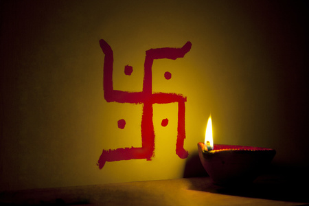 oil lamp: Earthen lamp lit in front of Hindu swastika symbol Stock Photo