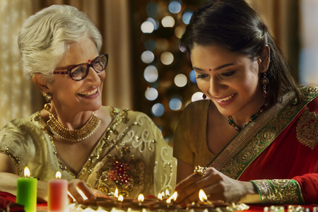 Daughter in law decorating the house with mother in law on the occasion of Diwali Stock Photo