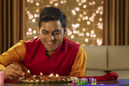 Man decorating the house with diyas on the occasion of Diwali
