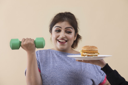 Excited Overweight Woman Exercising Cropped Hand Giving Burger