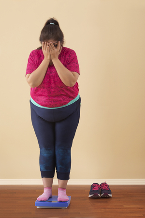Shocked Overweight Woman Standing On Measuring Scale Stock Photo