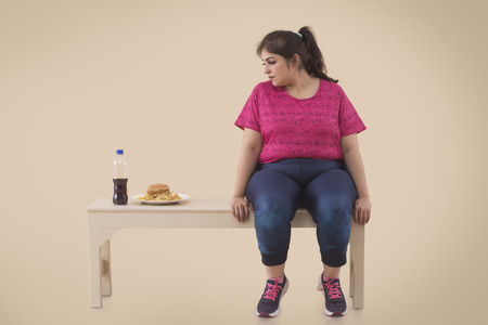 Overweight Woman is looking at the hamburger while resting after workout