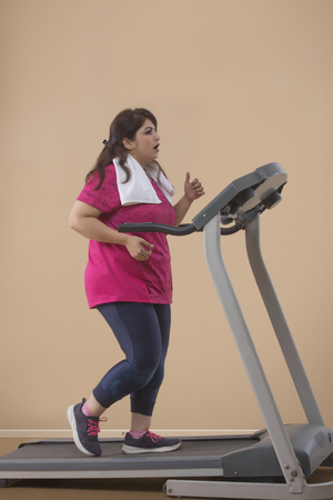 Fat Woman Doing Exercise On Treadmill in a gym