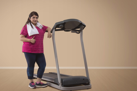 Portrait of Overweight woman standing with treadmill Stock Photo