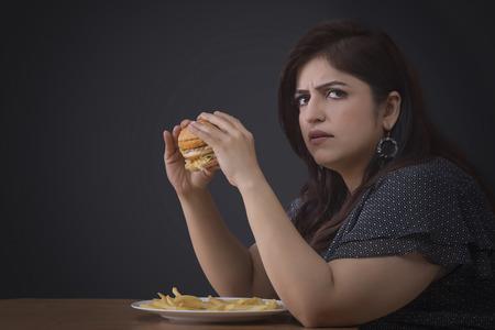 Angry Fat woman eating a hamburger