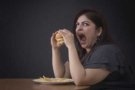 Angry irritated Fat woman eating a hamburger