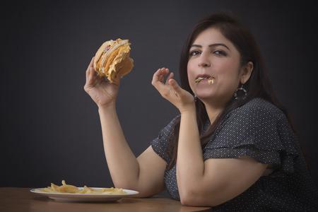 Fat woman eating a hamburger