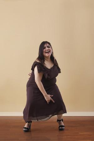 Fat woman in a long brown dress dancing on high heels