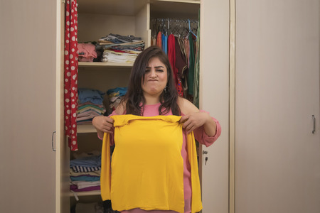 angry Fat woman trying to wear small size of yellow t-shirt