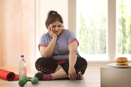fat woman making choice between exercising and unhealthy eating Stock Photo
