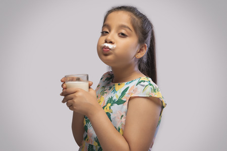 Side view of a girl having milk moustache drinking milk in a glass Stock Photo