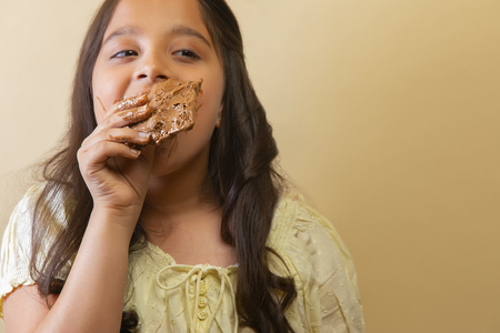 Girl eating a melting chocolate looking away