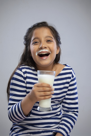 Portrait of a smiling girl with milk moustache holding a glass of milk