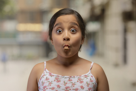 Portrait of a girl with a piece of chocolate in her mouth with eyes wide open and raised eyebrows Stock Photo