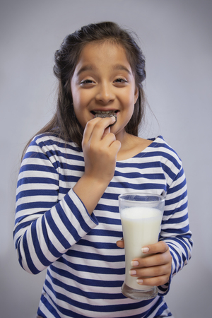 Happy girl eating a biscuit while holding a glass of milk