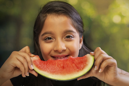 Close up of a girl eating a slice of watermelon holding with both hands Stock Photo