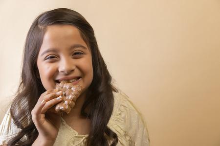 Smiling girl eating a chocolate bar