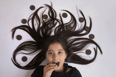 Close up of girl lying on floor eating biscuit with her hair arranged in a tree design with biscuits Stock Photo