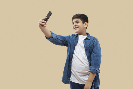 Teenage Boy Taking Selfie Through Mobile Phone While Standing Against color background Stock Photo