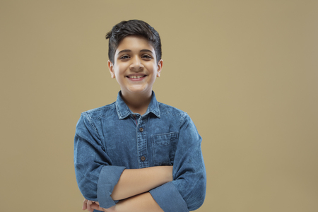 Portrait of smiling boy with crossed arms color background