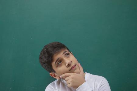 Close up portrait of boy thinking against on blackboard