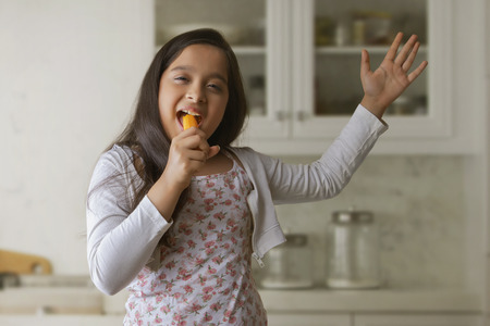 Girl eating carrot standing in kitchen holding it like a singer