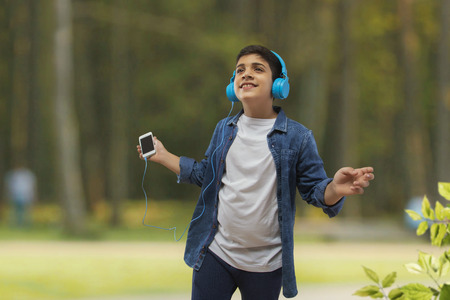 Boy with headphone dancing while listing to music on smartphone outdoors