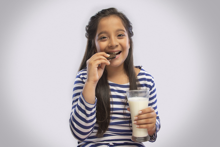 Smiling girl eating a cream biscuit while holding a glass of milk in one hand