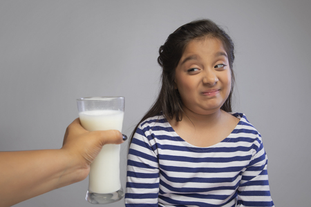 Girl making faces of dislike looking at the glass of milk being offered Stock Photo