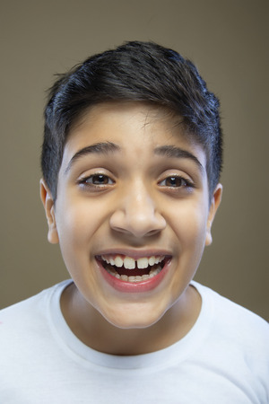 Close up portrait of cute little boy laughing against color background